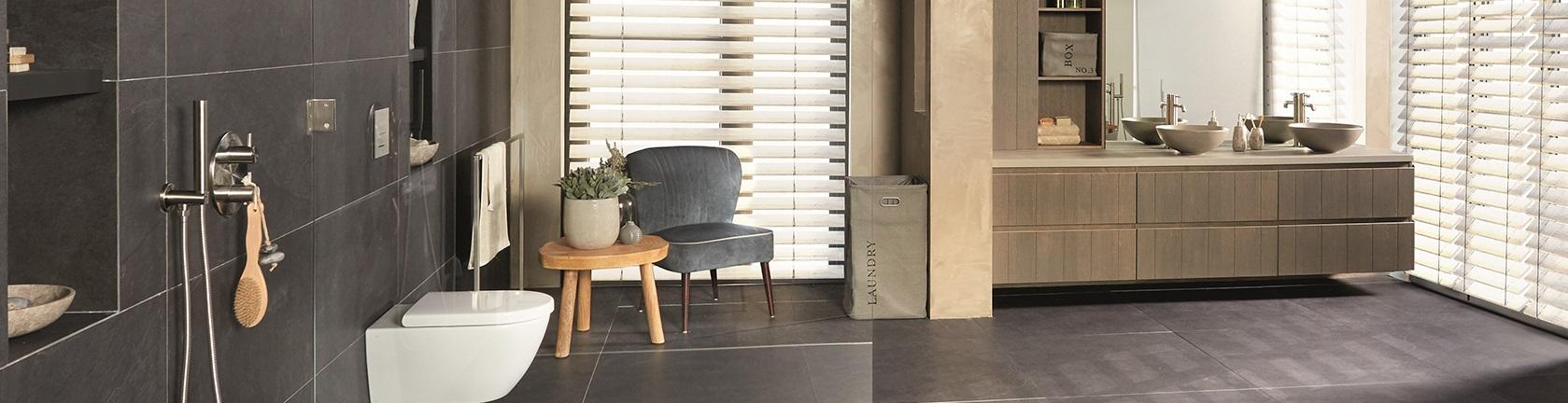 Badkamer voorzien van een toilet douche stoel wandmeubel in de kleuren grijs beige en hout